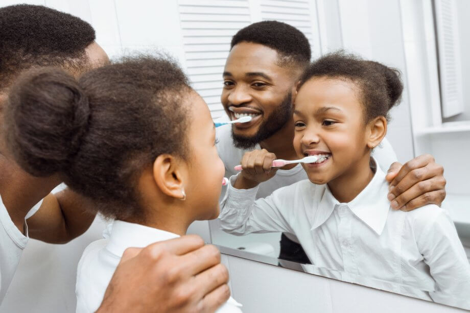 Father And Daughter Brushing Teeth Together Looking In Bathroom Mirror