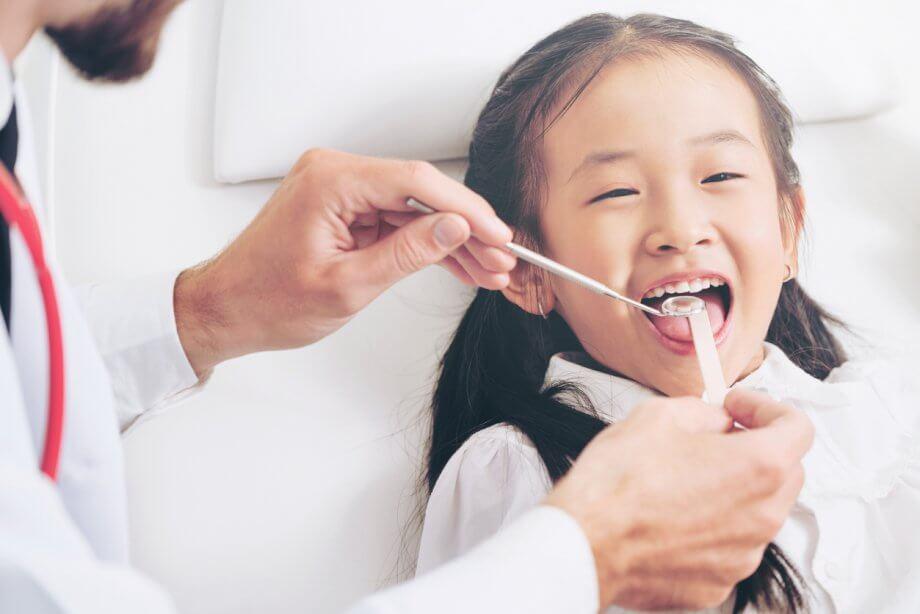 Dentist Examining Smiling Child's Teeth