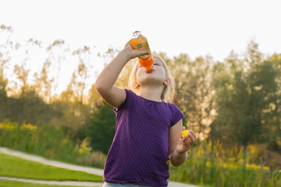 Young girl drinks juice from bottle