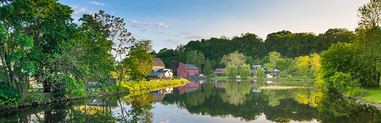 Panoramic view of red mill and pond in Clinton, New Jersey