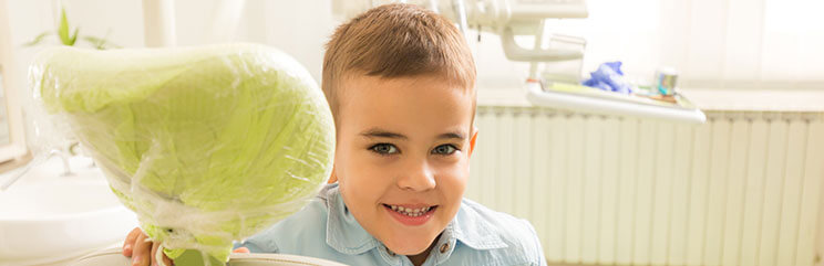 A young boy standing next to a dental exam chair smiling